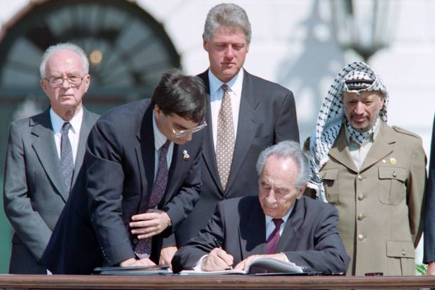 Mr. Peres, middle, the historic Oslo agreement at the White House on Sept. 13, 1993. Behind him are Israeli prime minister Yitzhak Rabin, an unidentified aide, U.S. president Bill Clinton and PLO chairman Yasser Arafat.