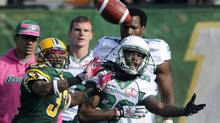 Saskatchewan Roughriders' Taj Smith (R) misses a pass under pressure from Edmonton Eskimos' Rod Williams during their CFL game in Edmonton October 13, 2012. (DAN RIEDLHUBER/REUTERS)