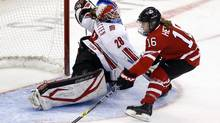 Canada's Jayna Hefford scores on Switzerland goalie Sophie Anthamatten in a 13-0 victory. (CHRIS WATTIE/REUTERS)
