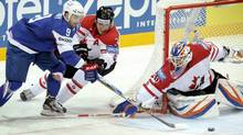 Damien Fleury of France, left, tries to score against Canada's Dion Phaneuf and goalie Devan Dubryk during their Ice Hockey World Championships in Helsinki (Antti Aimo-Koivisto/Associated Press)
