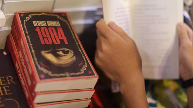 This file photo taken on July 15, 2015 shows a boy reading a book next to copies of British writer George Orwell's 1984 at Hong Kong's annual book fair.