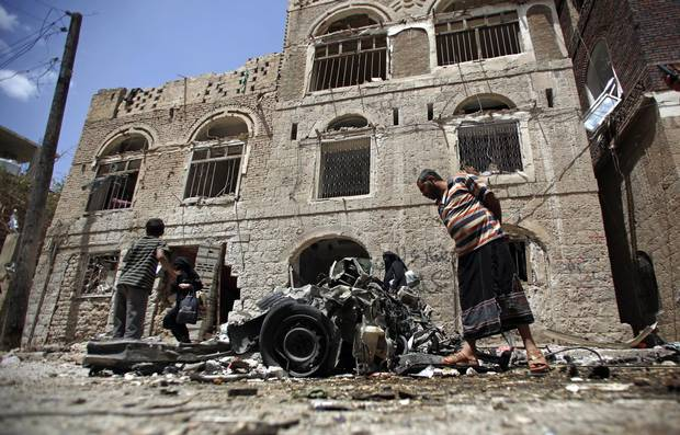 People stand amid wreckage of a vehicle at the site of a car bomb attack near a military hospital in Sanaa, Yemen, in January, 2015.