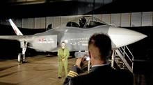 A Canadian Forces pilot has his picture taken in front of a F-35 fighter mock-up prior to a procurement announcement in Ottawa on July 16, 2010. (Adrian Wyld/Adrian Wyld/The Canadian Press)
