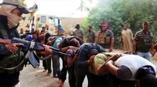 Este sábado, 14 de junio, la imagen de archivo de 2014 en un sitio web militante que ha sido verificado y es consistente con otros reportes de AP, parece mostrar militantes del grupo Estado Islámico principales soldados iraquíes lejos capturados vestidos de civil tras hacerse cargo de una base en Tikrit, Iraq.  (No acreditado / LA PRENSA ASOCIADA)