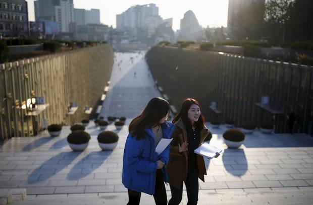 University students talk as they leave Ewha Campus Complex of Ewha Woman's University in Seoul, South Korea.