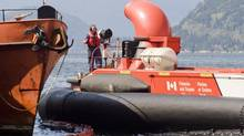 A Coast Guard hovercraft helps contain spilled oil and diesel fuel after a tugboat sank at a dock at Britannia Beach near Vancouver on May 9, 2008. (Brian Thompson for The Globe and Mail)
