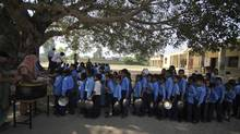 Indian schoolchildren line up for a free midday meal at a government school on the outskirts of Jammu, India, on Tuesday, Oct. 9. The United Nations now says its 2009 headline-grabbing announcement that 1 billion people in the world were hungry was off-target and that the number is actually more like 870 million. (Channi Anand/Associated Press)