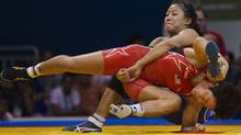 Canada's Carol Huynh upends Clarissa Chun of the U.S. during the gold medal match for women's 48kg wrestling at the Pan American Games in Guadalajara October 22, 2011. Huynh won the bout. The Games run through October 30. REUTERS/Andy Clark (Andy Clark/Reuters)