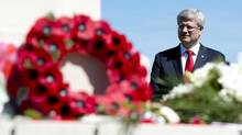 Prime Minister Stephen Harper stands in front of the cenotaph in the Canadian military cemetery in Beny-sur-Mer, France. (Adrian Wyld/THE CANADIAN PRESS)