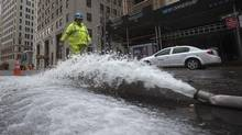 A worker walks past a hose pumping water out of underground parking structures in the financial district of Lower Manhattan Oct. 30, 2012. Major stock exchanges will reopen Wednesday. (ADREES LATIF/REUTERS)