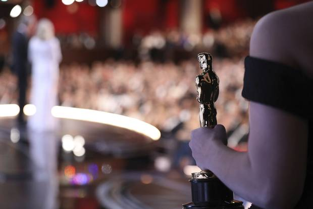 One of the best picture Oscar statuettes appears offstage as Warren Beatty and Faye Dunaway announce the Best Picture winner.