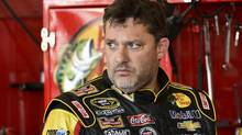 In this Friday, Aug. 8, 2014 photograph, Tony Stewart stands in the garage area after a practice session for Sunday's NASCAR Sprint Cup Series auto race at Watkins Glen International, in Watkins Glen N.Y. (Derik Hamilton/AP)