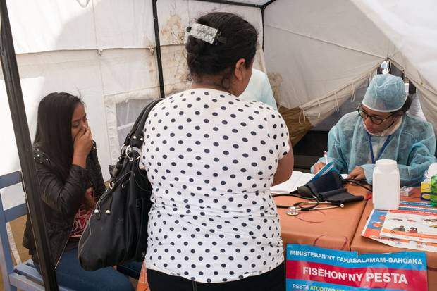 A young woman, left, gestures as she is examined by doctors at the health-care checkpoint.