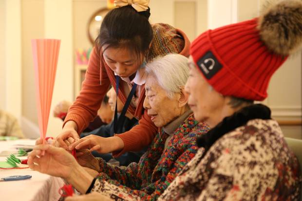 Staff at a Beijing dementia care ward run by Senior Living L'amore lead residents through daily activities.