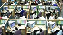 Indian employees work at a call centre in the southern Indian city of Bangalore in this file photo. The CRTC said Wednesday it was putting foreign telemarketers 'on notice.' (STR/REUTERS)