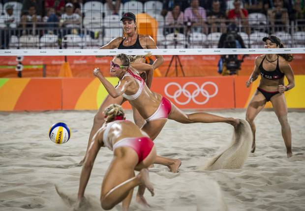 Canadians Heather Bansley and Sarah Pavan scramble for the ball after a successful spike by Swiss players Nadine Zumkehr and Joana Heidrich in preliminary beach volleyball action at Rio Olympics August 10, 2016. (John Lehmann/The Globe and Mail)