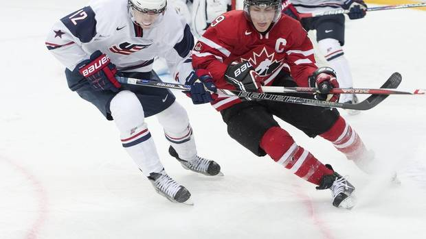 Team Canada forward Ryan Hugent-Hopkins, right, battles for the loose puck against Team USA forward Mario Lucia, left, during second period IIHF World Junior Championships hockey action in Ufa, Russia on Sunday, Dec. 30, 2012. (Nathan Denette/THE CANADIAN PRESS)