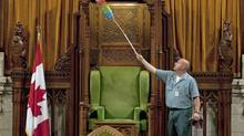 A worker dusts the Speaker's chair on Sept. 16, 2010, as the House of Commons chamber is prepared for the resumption of Parliament in Ottawa. (Adrian Wyld/The Canadian Press)