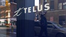 Pedestrian is reflected in the window of a Telus shop in Ottawa. (Chris Wattie/Reuters)