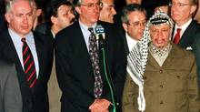 "Palestinian President Yasser Arafat, right, and Israeli Prime Minister Benjamin Netanyahu, left, listen as United States special envoy Dennis Ross speaks about the agreement reached and initialed early January 15, 1997, concluding the long overdue Hebron troop redeployment talks, as well as other issues contained in an American ""note for the record"" which deals with future Israeli redeployments and other non-Hebron related issues. The talks lasted less than two hours and concluded months of negotiations which will lead to the end of the Israeli military occupation in about 80 percent of Hebron. (Havakuk Levison/REUTERS)"