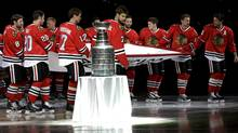 The Chicago Blackhawks carry out the Stanley Cup Championship banner past the Stanley Cup during a ceremony before an NHL hockey game between the Blackhawks and the Washington Capitals Tuesday, Oct. 1, 2013, in Chicago. (Associated Press)