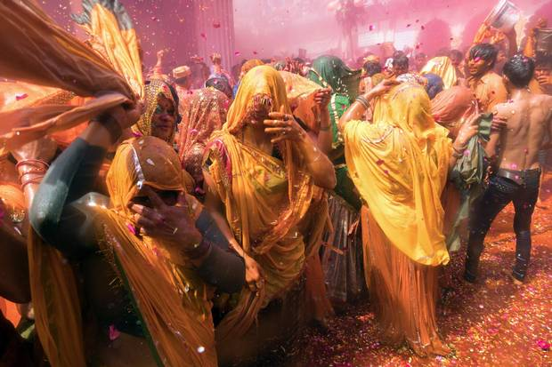 A Dauji woman lashes the author with a towel as part of a playful tradition known as Huranga, which goes back more than 500 years. Men drench women with buckets of coloured water; women strip and beat the men.