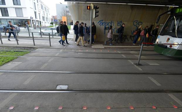 Traffic lights are embedded in the streets to warn pedestrians using their phones in Augsburg, Germany.