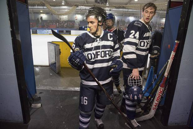 Oxford Blues hockey player Joey Wening checks his stick after leaving the ice between periods on March 3, 2018.