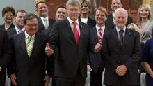 Canadian Prime Minister Stephen Harper gestures as she stands with members of his Cabinet following a swearing in ceremony at Rideau Hall in Ottawa on Monday, July 15, 2013. (Adrian Wyld/THE CANADIAN PRESS)