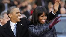 U.S. President Barack Obama and first lady Michelle Obama walk and wave after emerging from the presidential limousine during the inaugural parade from the Capitol to the White House in Washington, Jan. 21, 2013. (LARRY DOWNING/REUTERS)