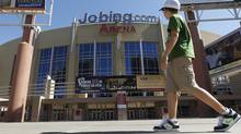 A lone pedestrian walks past Jobing.com Arena, Wednesday, June 13, 2012, in Glendale, Ariz., where the Phoenix Coyotes NHL hockey team plays home games. (Associated Press)