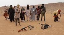 Islamist rebels from the Ansar Dine faction prepare to pray in the desert just outside Gao, Mali, in May. (Diakaridia Dembele/The Associated Press)