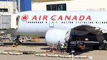 An Air Canada Boeing 777 sits at a gate after it was forced to return to Sydney Airport in Sydney, Thursday, July 28, 2011, after crew members saw smoke coming from an oven in the galley. (Rick Rycroft/AP)