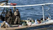 """Two sailors from HMCS Toronto's boarding team keep a watch over the crew of a """"dhow"""" style fishing during a search for evidence connecting them to terrorism. This was HMCS Toronto's first operational vessel inspection of Operation Altair, and found a fully co-operative captain and crew with no improper cargo. (MCpl Colin Kelley/Handout-DND/MCpl Colin Kelley/Handout-DND)"""