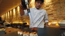 Sous chef Naoki Kasai prepares a samplings dish which is finished with a blowtorch. (DEBORAH BAIC/THE GLOBE AND MAIL)