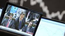A news story about British Prime Minister David Cameron is broadcast on a TV screen at the stock market in Frankfurt, Germany, Monday, Dec. 12, 2011, when the German stock index DAX went down more than 2 per cent. (Michael Probst/Michael Probst/AP)