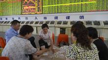 Investors play cards in front of an electronic board showing stock information and a row of computers at a brokerage house in Taiyuan, Shanxi province July 5, 2012. China's main stock index closed 1.2 percent lower on Thursday, dampened by weakness in energy and material companies on worries of a further slowdown in the domestic economy. (REUTERS)