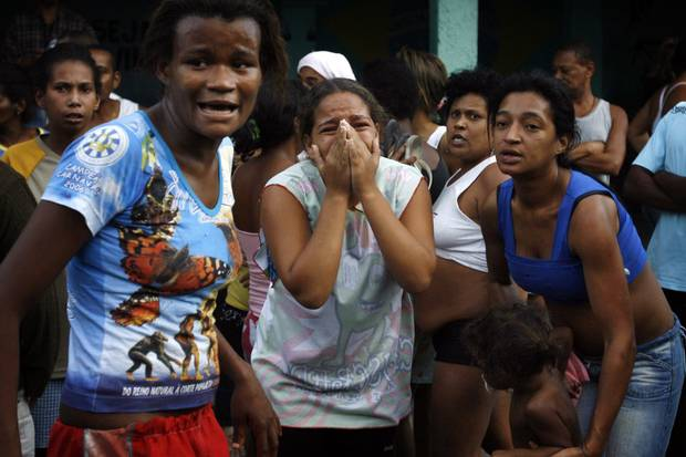 Residents react during a shootout involving police and suspected drug traffickers at the Complexo de Alemao slum in Rio de Janeiro on June 27, 2007. Police killed at least 18 suspected drug traffickers in the massive operation.