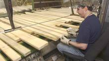 A lumber grader at Tolko Industries in Kelowna sorts lumber in 2006 destined for the U.S. market. (GARY NYLANDER/The Canadian Press)