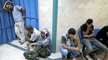 Libyan rebel fighters mourn comrades killed during clashes with forces loyal to Muammar Gaddafi at a hospital in Misrata July 11, 2011. (THAIER AL-SUDANI/REUTERS/THAIER AL-SUDANI/REUTERS)