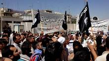 Demonstrators chant pro-al-Qaida-inspired Islamic State of Iraq and the Levant (ISIL) as they wave al-Qaida flags in front of the provincial government headquarters in Mosul, 360 kilometers northwest of Baghdad, Iraq, Monday, June 16, 2014. (AP)