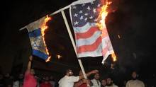 Lebanese Muslim protesters burn the American and Israeli flags during a protest about a film ridiculing Islam's Prophet Muhammad, in the southern port city of Sidon, Lebanon, Thursday, Sept. 13, 2012. (Mohammad Zaatari/AP)