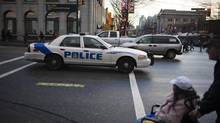A police car patrols as people wait to cross Main Street and East Hastings Street in the Downtown Eastside in Vancouver, British Columbia, Tuesday, December 18, 2012. (Rafal Gerszak For The Globe and Mail)