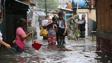 Residents wade through floods as they go back to their homes while Typhoon Rammasun batters suburban Quezon city, north of Manila, on July 16, 2014. (AARON FAVILA/ASSOCIATED PRESS)