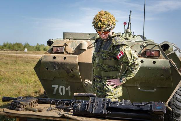 A Canadian soldier examines an automatic APC cannon before a drill in Yavoriv, Ukraine. Canadian trainers are helping Ukraine modernize its tactics to combat pro-Russian separatists.