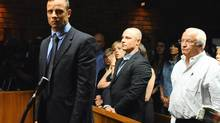 Oscar Pistorius, foreground, stands after his Feb. 19 bail hearing in Pretoria as his brother, Carl, middle, and father, Henke, right, look on. (Masi Losi/AP)