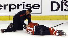 Chicago Blackhawks' Marian Hossa lies on the ice after being injured following a check by Phoenix Coyotes' Raffi Torres during Game 3 of their NHL Western Conference quarter-final playoff hockey game in Chicago. (JIM YOUNG/Reuters)