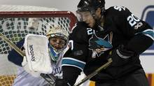 Vancouver Canucks goalie Roberto Luongo (L) blocks a shot as San Jose Sharks Kyle Wellwood moves in. REUTERS/Mike Blake (MIKE BLAKE)