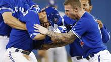 Toronto Blue Jays' Jose Bautista (L) is congratulated by team mate Brett Lawrie (R) after getting walk off single to beat the Tampa Bay Rays during the tenth inning of their American League baseball game in Toronto May 22, 2013. (MARK BLINCH/REUTERS)