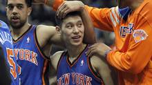 New York Knicks' guard Jeremy Lin (17) is congratulated by teammates Jerome Jordan (R) and Landry Fields (L) after the Knicks defeated the Minnesota Timberwolves 100-98 in their NBA basketball game at the Target Center in Minneapolis February 11, 2012. (ERIC MILLER/Reuters)